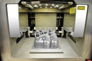 The view into the interior of the 3D printer shows the first printed thermostat covers, which are still connected to the work platform. After removal of the platform and support structure, the aluminium/silicon metallic powder is removed by suction, sieved, cleaned and ecologically fed back into the recycling system.